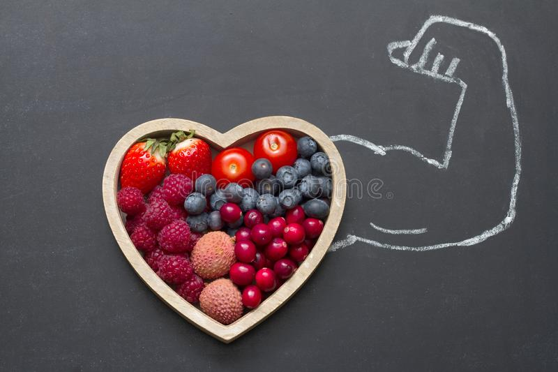 Health diet heart abstract concept with strongman hand on blackboard royalty free stock image