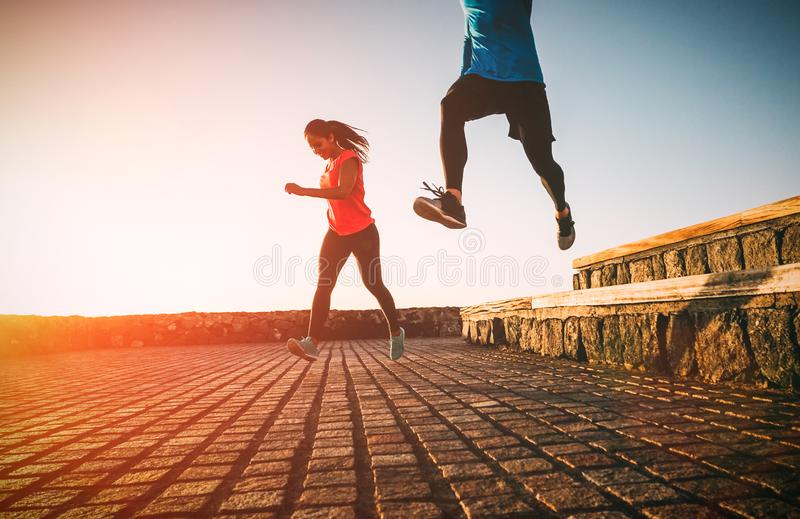 Health fit young couple running together during a magnificent sunset - Athletic friends doing sport outdoor stock photography