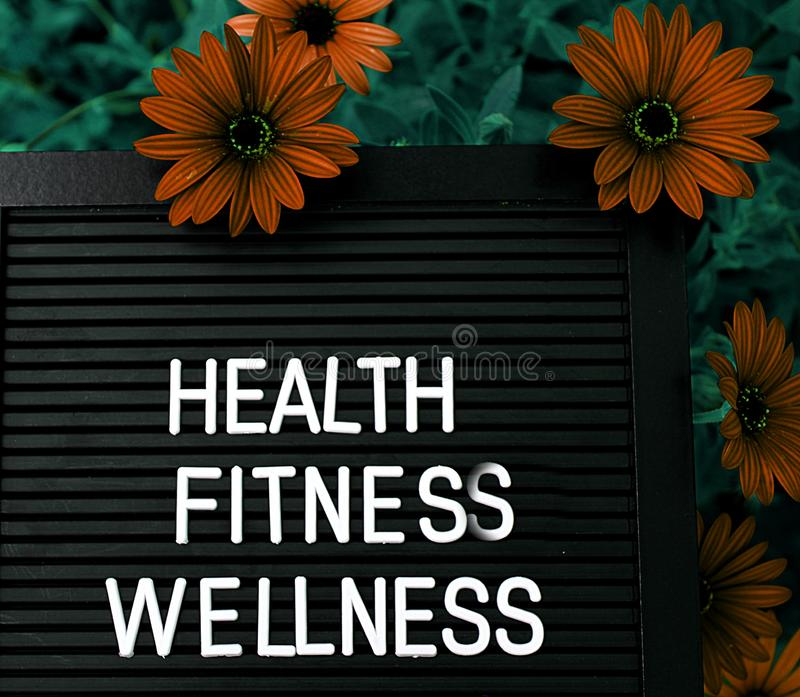 Health, Fitnes, Wellness - Heathy concept - Isolated text on black background with colorful flowers. Heathy concept - Isolated text on black background with royalty free stock image