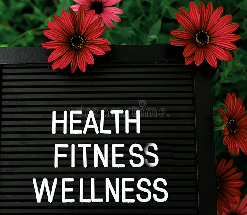Health, Fitnes, Wellness - Heathy concept - Isolated text on black background with colorful flowers. Heathy concept - Isolated text on black background with stock images
