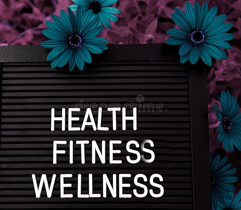 Health, Fitnes, Wellness - Heathy concept - Isolated text on black background with colorful flowers. Heathy concept - Isolated text on black background with stock photos