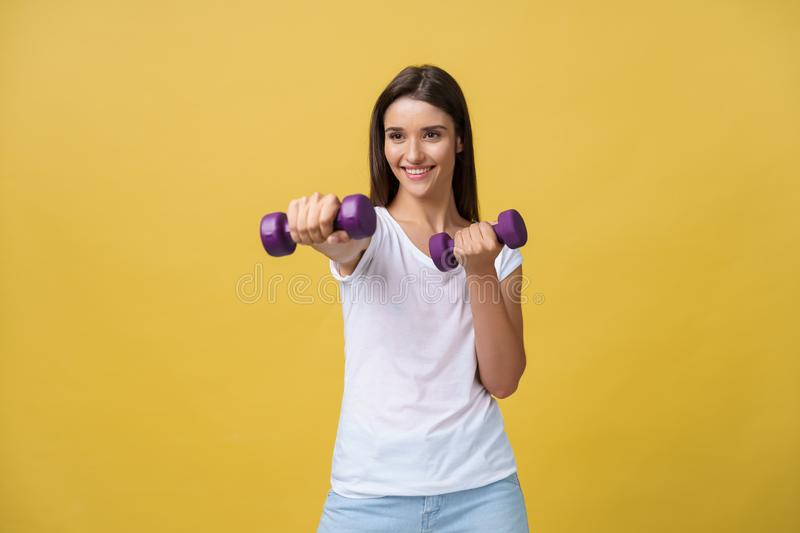 Health and Fitness Concept: Shot of a beautiful and sporty young woman lifting up weights against yellow background. royalty free stock photos