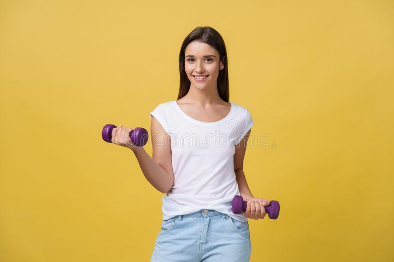 Health and Fitness Concept: Shot of a beautiful and sporty young woman lifting up weights against yellow background. stock photos