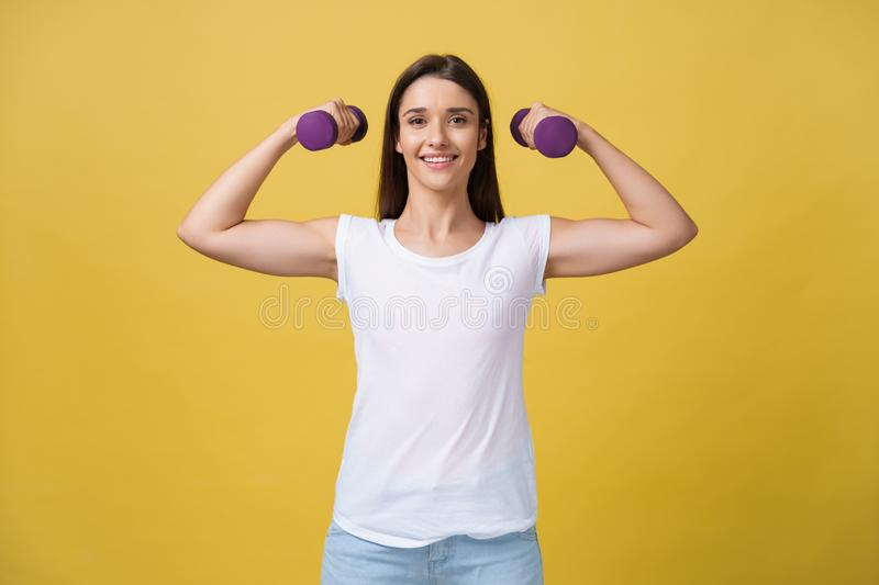 Health and Fitness Concept: Shot of a beautiful and sporty young woman lifting up weights against yellow background. royalty free stock image