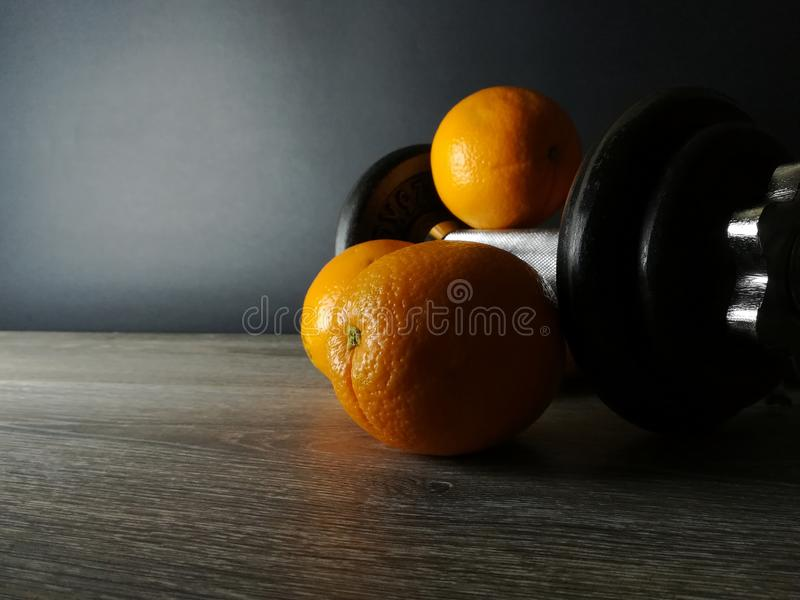Orange with weights, health and fitness stock photography