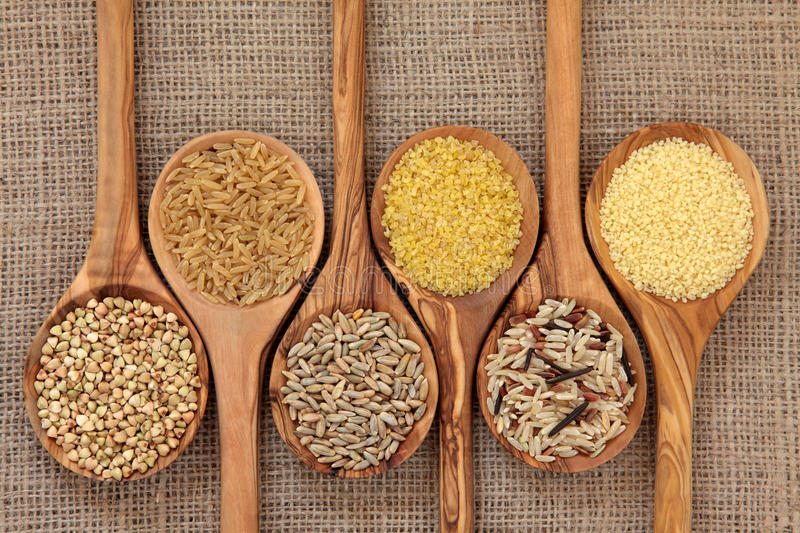 Health Food. Cereal and grain selection of bulgur wheat, buckwheat, couscous, rye grain and brown and wild rice in olive wood spoons on hessian sacking stock photography