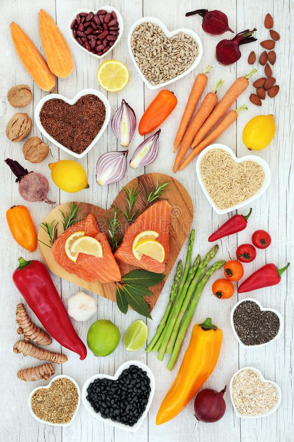 Health Food for Heart Fitness. Concept with superfoods of salmon fish, fruit, vegetables, grain, pulses, seeds, nuts, spice and herbs providing high levels of royalty free stock photos