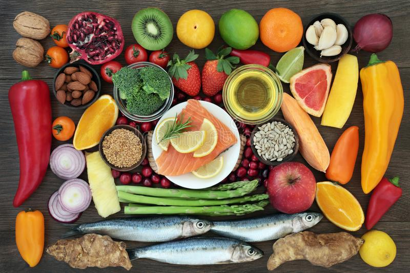 Health Food High in Nutrients. Health food for a healthy heart concept with fresh sardines, salmon, vegetables, fruit, nuts, seeds, herbs and olive oil stock photos