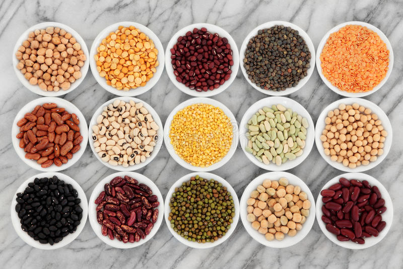 Health Food. Pulses health food selection in white porcelain dishes over marble background royalty free stock image
