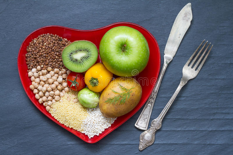 Health food on a red heart plate diets abstract still life. Concept stock image