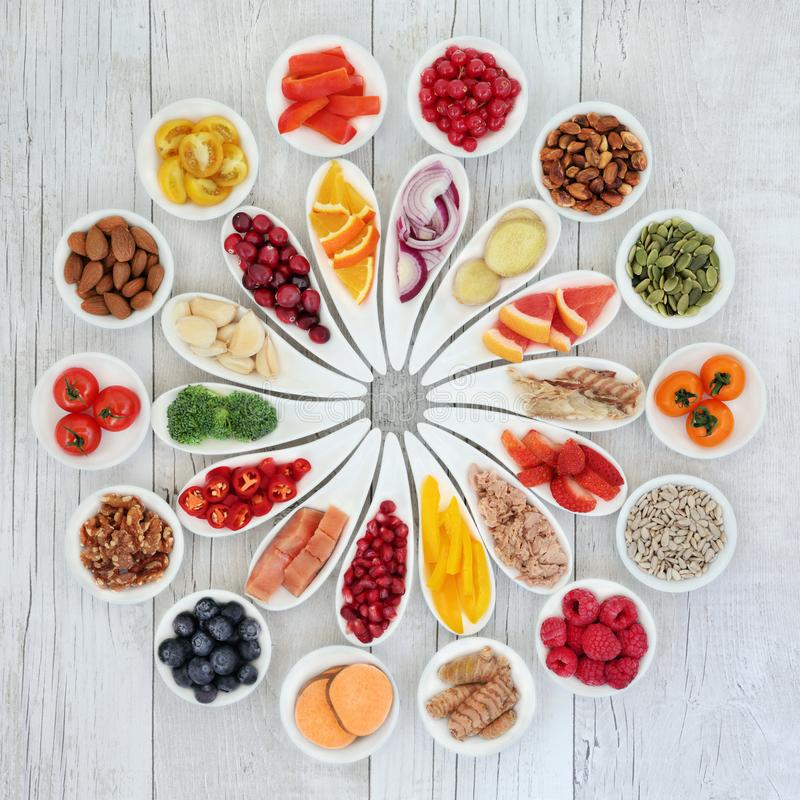 Health Food Selection. Health food for a healthy heart concept with super foods of fruit, vegetables, fish, nuts, seeds, herbs and spices providing high levels stock image