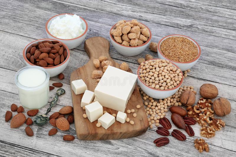 Health Food for Vegans. With tofu, soybeans, nuts, seeds, soya yoghurt, milk and chunks, Foods high in fiber, antioxidants, vitamins and minerals, on rustic stock images