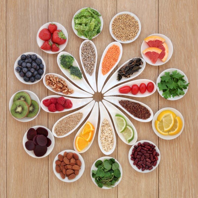 Health Food Wheel. Health detox super food selection in porcelain bowls over oak wood background stock images