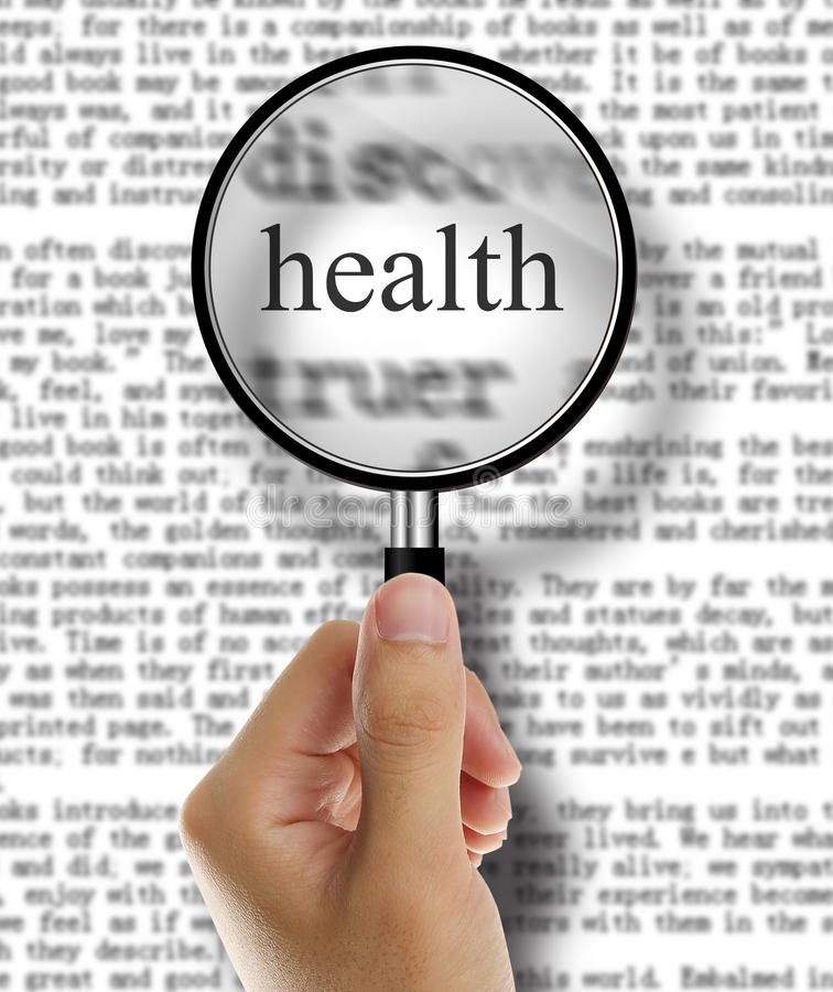 Health. Hand holding magnifying glass look at health text stock image