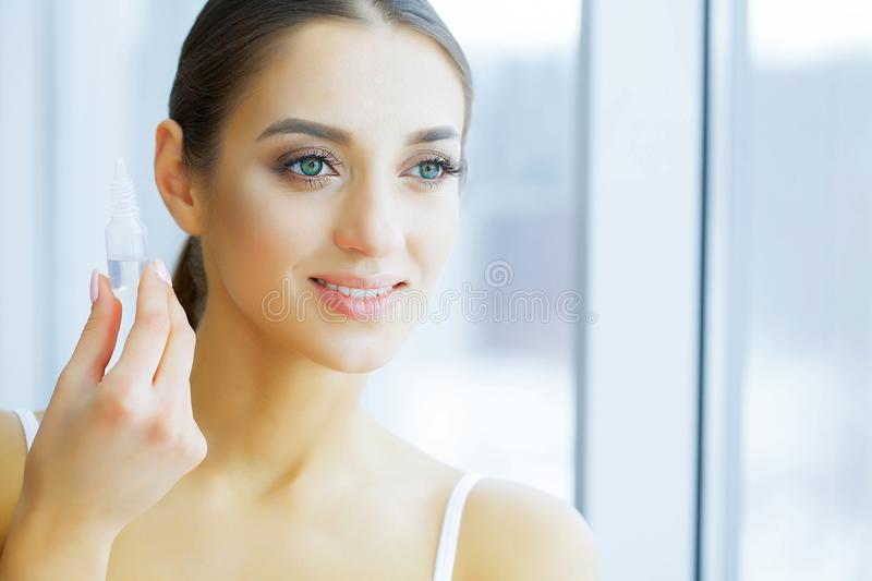 Health. Happy Girl with Fresh Look. Eye Care. Beautiful Young Woman Holding Drops For Eyes. Good Vision. Girl with Green Eyes. Hi royalty free stock images