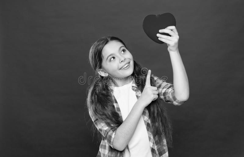 Health and healthcare. Having heart problem and heartache. Small girl pointing finger at red heart. Little child. Expressing love on valentines day. Cute girl stock photography