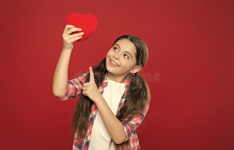 Health and healthcare. Having heart problem and heartache. Small girl pointing finger at red heart. Little child. Expressing love on valentines day. Cute girl royalty free stock photo