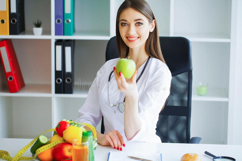 Health. Healthy Diet. Doctor Dietitian Holding in Hands Fresh Gr. Een Apple and Smiles. Beautiful and Young Doctor. High Resolution royalty free stock photo