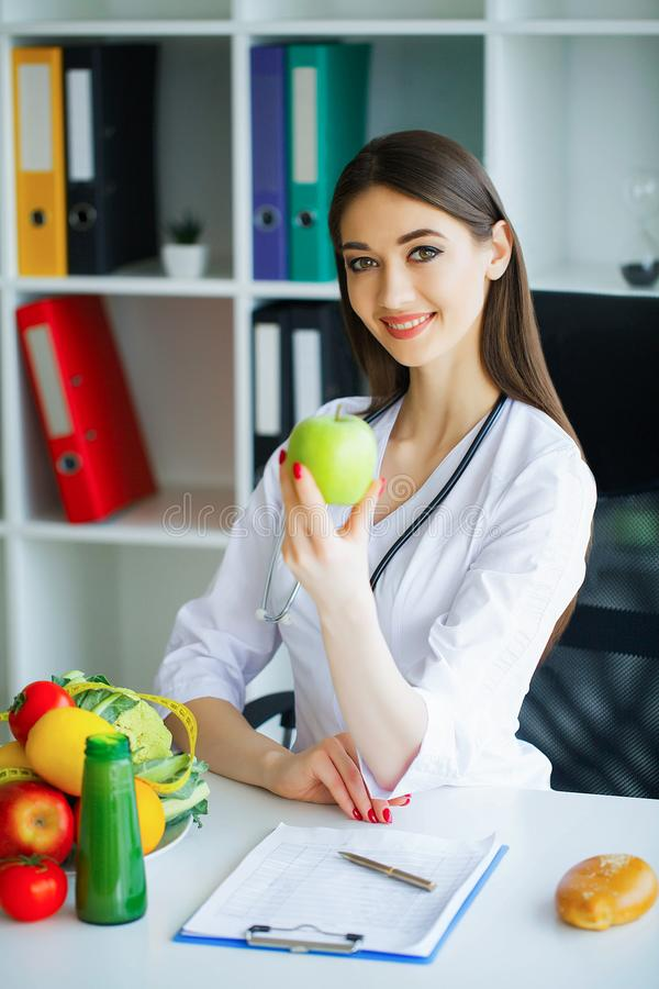 Health. Healthy Diet. Doctor Dietitian Holding in Hands Fresh Gr. Een Apple and Smiles. Beautiful and Young Doctor. High Resolution royalty free stock images