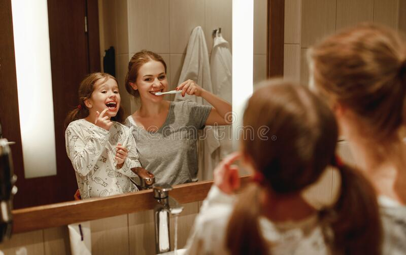 Health and hygiene of oral cavity. mother and child daughter brush their teeth in   bathroom in front of a mirror stock image