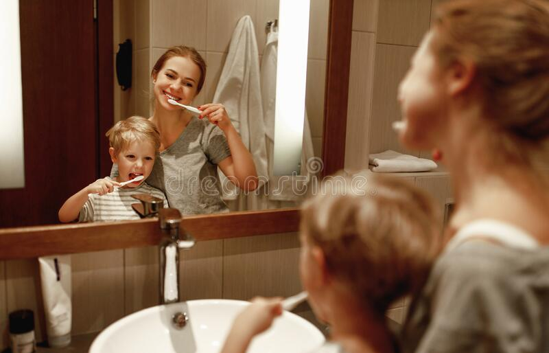 Health and hygiene of   oral cavity. mother and child son brush their teeth in   bathroom in front of a mirror royalty free stock images