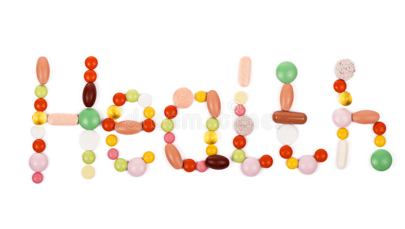 Health inscription made from pills. Health inscription made from colorful pills on white stock image