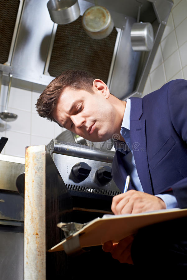 Health Inspector Looking At Oven In Commercial Kitchen royalty free stock photography