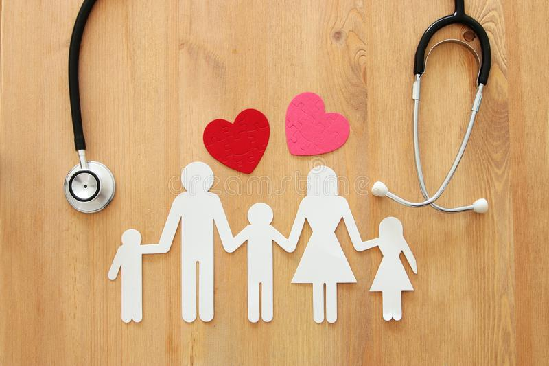 Health Insurance . concept image of Stethoscope and family on wooden table. top view. royalty free stock image