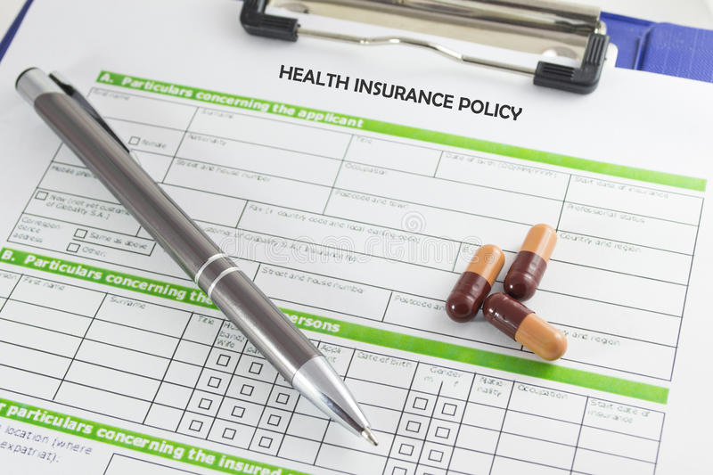 Health insurance. Pen and pills on blue clipboard with health insurance policy form. Health insurance concept royalty free stock photography