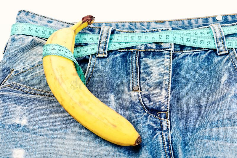 Health and male sexuality concept: kinky fruit on denim trousers. Health and male sexuality concept. Kinky fruit on denim trousers, close up. Pants with banana royalty free stock images