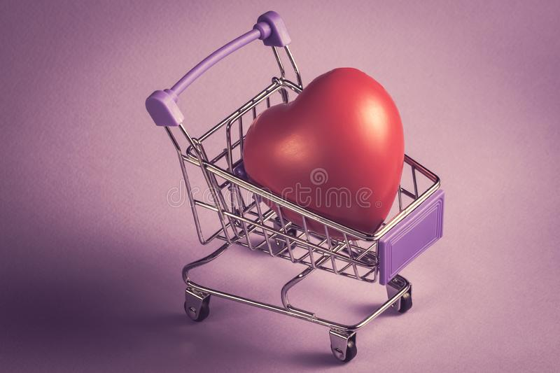 Health, medicine and charity concept - close up heart in shopping cart ,romance or valentine`s gift, on vintage purple  backgroun royalty free stock image