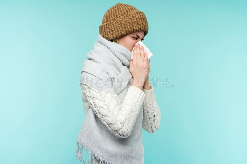 Health and medicine concept - Young woman blowing nose into tissue, on a blue background. Pretty girl cold with snot stock image