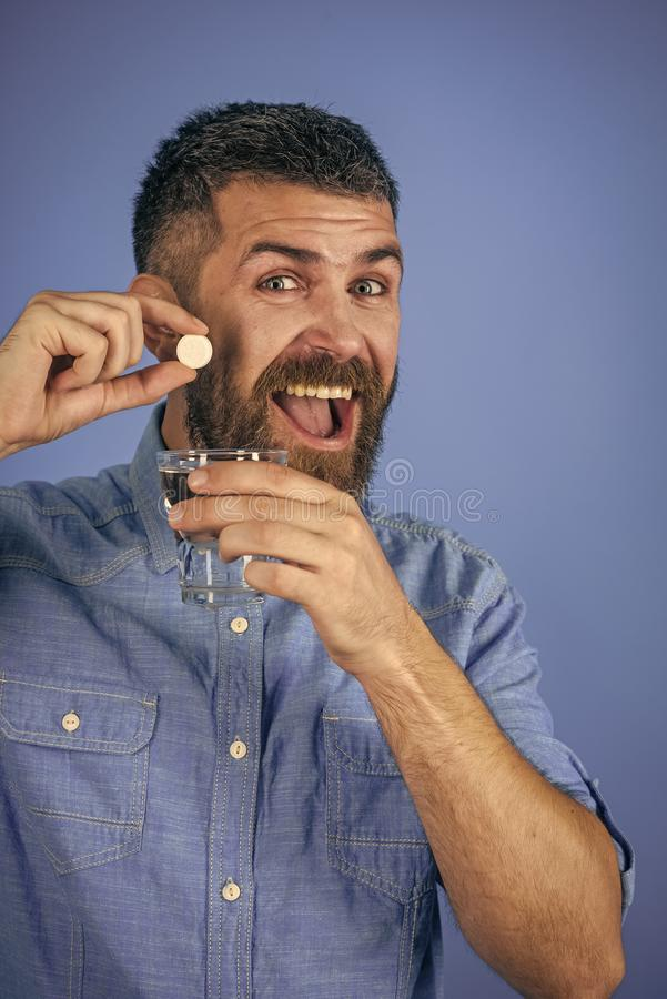 Health and medicine, flu and cold. Man with beard hold water glass on blue background, headache. painkiller drug and antidepressant. happy hipster drink pill royalty free stock images
