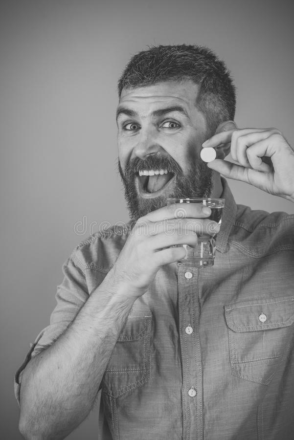 Health and medicine, flu and cold. Man with beard hold water glass on blue background, headache. painkiller drug and antidepressant. happy hipster drink pill royalty free stock image