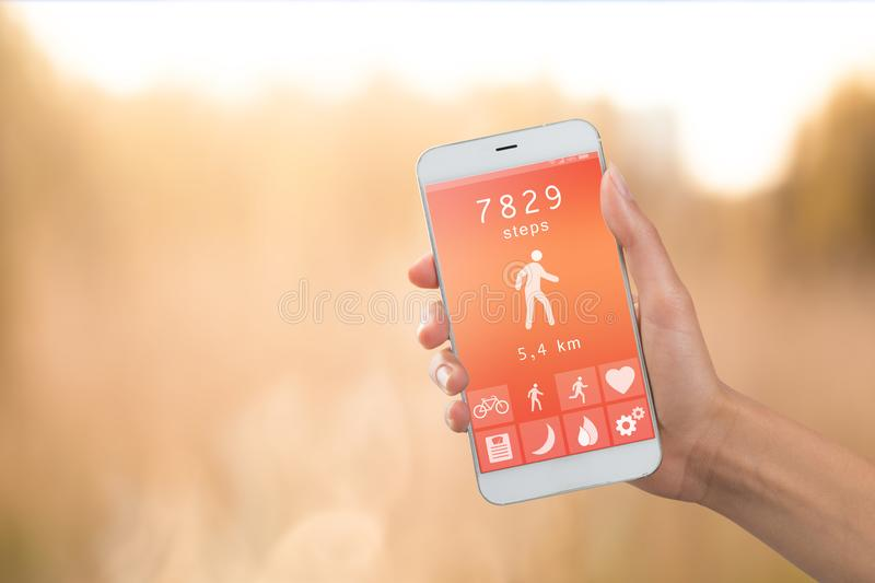 Health monitoring concept - special app on smartphone in a hand outdoors, landscape background stock images