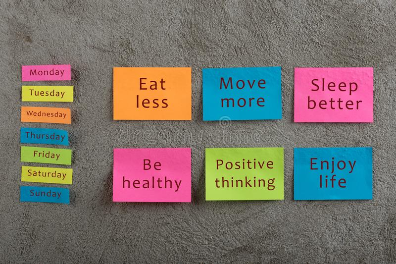 Health and motivation concept - Many colorful sticky note with words eat less, move more, sleep better, be healthy, positive. Thinking, enjoy life and days of royalty free stock photo