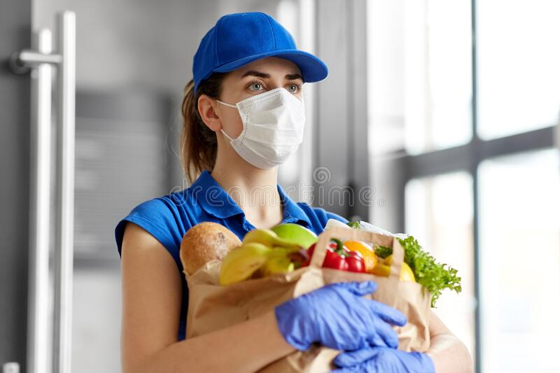 Delivery woman in face mask with food in paper bag. Health protection, safety and pandemic concept - delivery woman in face mask and gloves holding paper bag stock images