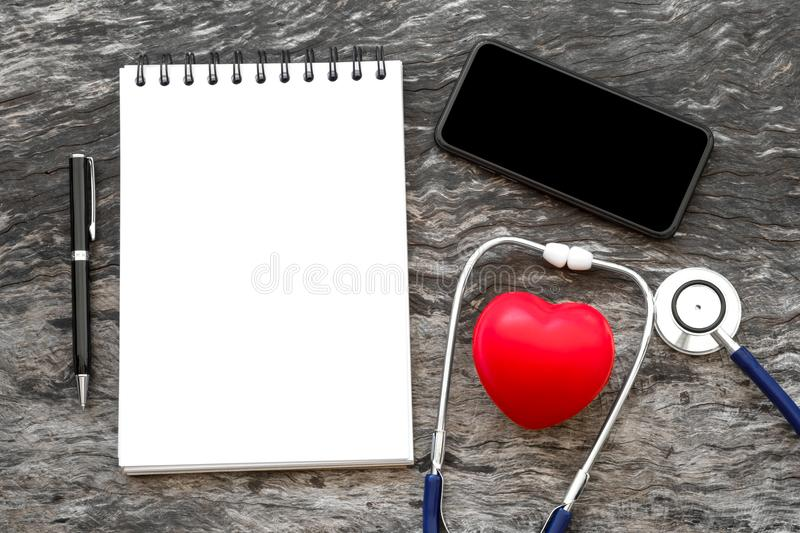 Health red heart with stethoscope and blank notebook for input s. Ome text with pen and blank screen of smartphone on wooden background with copy space. World royalty free stock image