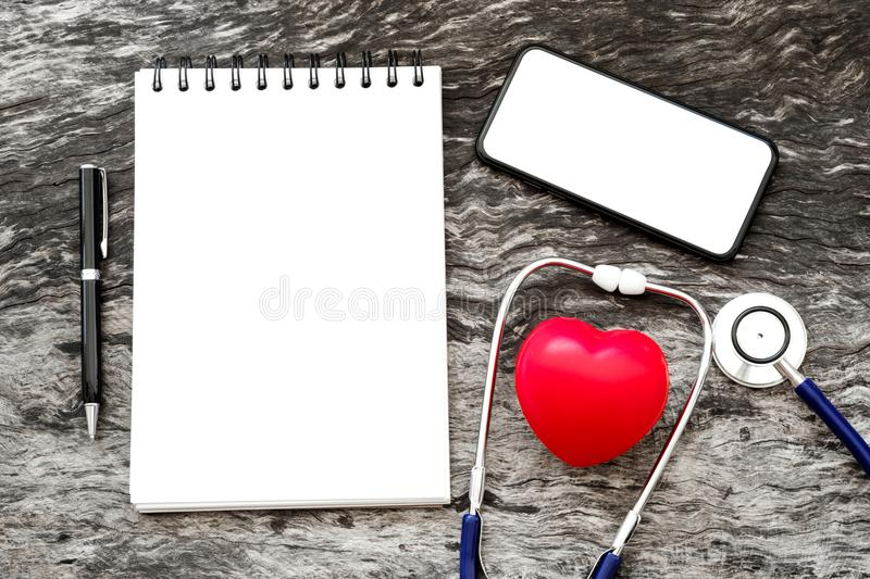 Health red heart with stethoscope and blank notebook for input s. Ome text with pen and blank screen of smartphone on wooden background with copy space. World stock image