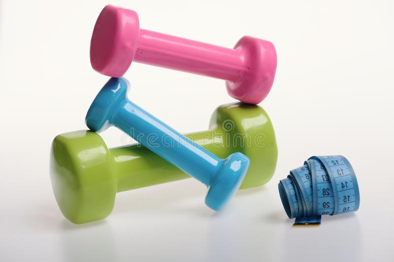 Measure tape and pink, green and blue barbells royalty free stock photography