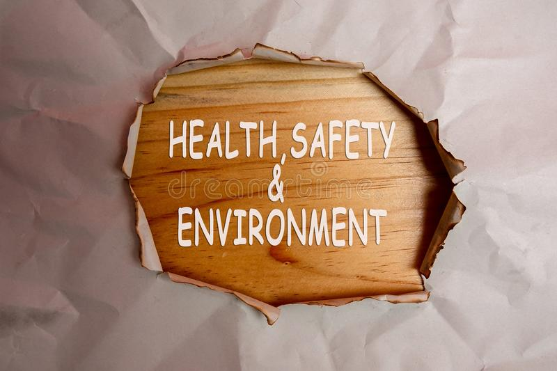 HEALTH, SAFETY AND ENVIRONMENT CONCEPT text at plain torn paper. HEALTH, SAFETY AND ENVIRONMENT CONCEPT text at plain torn paper stock photography