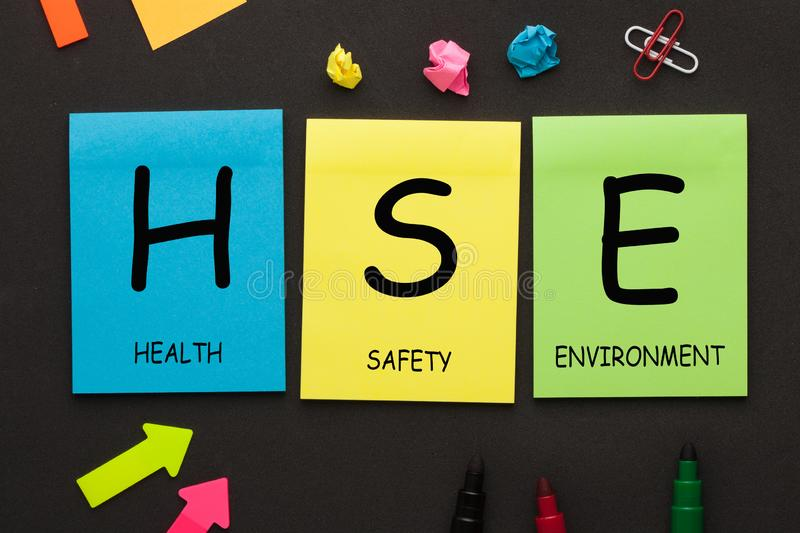 Health Safety Environment - HSE text on color notes. Health Safety Environment HSE text on color notes and office supplies on black background royalty free stock photo