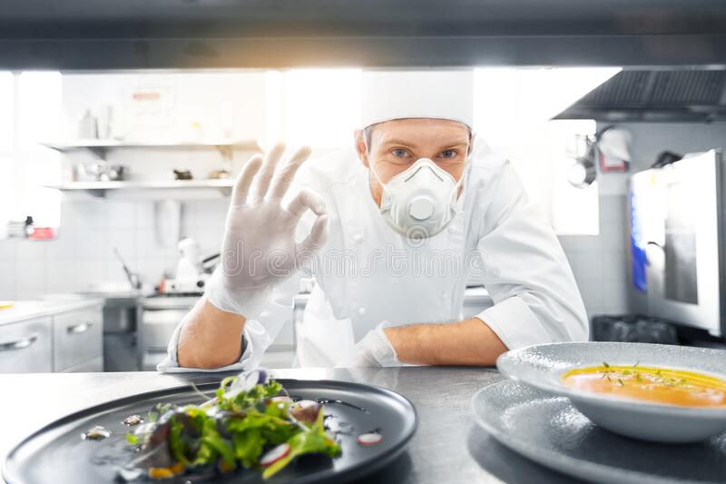 Male chef in mask with food at restaurant kitchen. Health, safety and pandemic concept - male chef cook wearing face protective mask or respirator for protection royalty free stock images