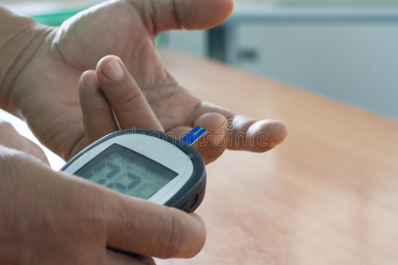 Health screening. Man holding measuring blood sugar levels with him own. The concept of self-care stock images