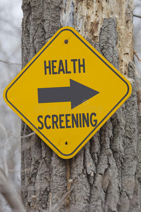 Health Screening this Way. A yellow sign on a tree showing which way for Health Screening making a great employer health insurance screening concept stock photography
