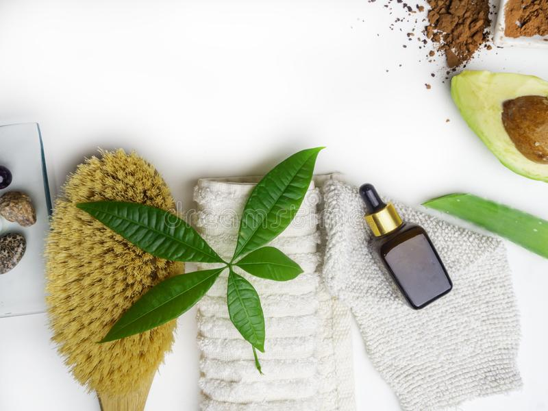 Health spa with massage serum, scrub, avocado, green aloe vera, leaf, massage acessories, towel, glove, brush on white background. Copy space royalty free stock photo