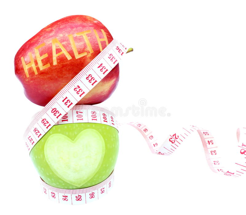 Health text and Heart shape on apple with white background, measuring tape wrapped around. Health text and Heart shape on apple with white background and royalty free stock photos