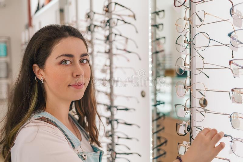 Health and vision. Young beautiful woman choose glasses in optical store royalty free stock photography