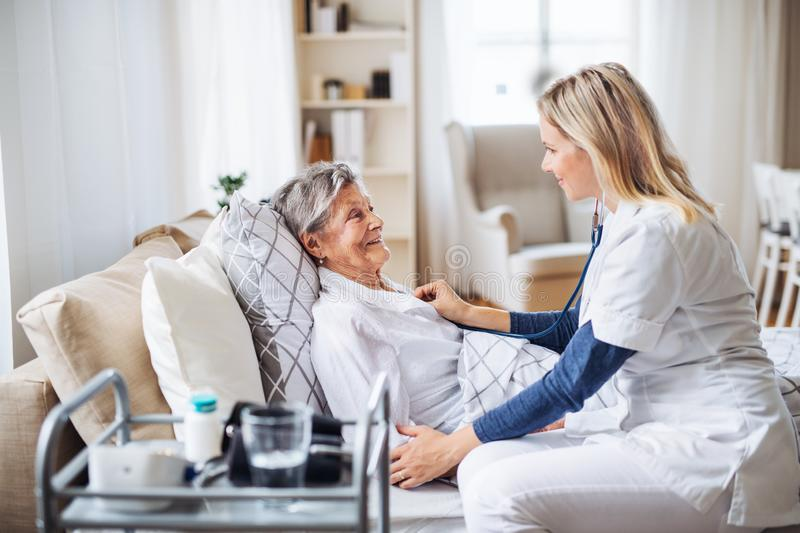 A health visitor examining a sick senior woman lying in bed at home with stethoscope. royalty free stock photos