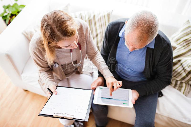 Health visitor and a senior man with tablet during home visit. stock images